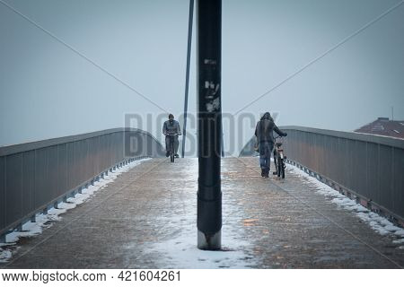 Sremska Mitrovica, Serbia - January 24, 2016: Two People, Man And Woman, Cycling With Their Bicycle