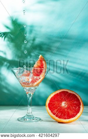 Refreshing Cocktail With Grapefruit On A Green Background. A Glass With Ice And Pieces Of Grapefruit
