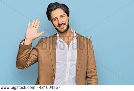 Young hispanic man wearing business clothes waiving saying hello happy and smiling, friendly welcome gesture