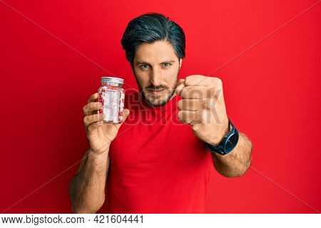 Young hispanic man holding jar of pills annoyed and frustrated shouting with anger, yelling crazy with anger and hand raised