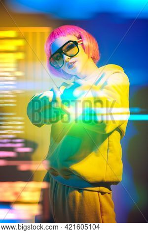 Modern girl with bright pink hair poses in yellow sunglasses and yellow suit in mixed color light. Sport chic fashion. Youth fashion and beauty trends.