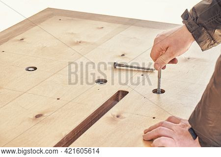 Skilled Craftsman Assembles Large Wooden Dining Table Turning Bolts With Hand Outdoors On Sunny Day