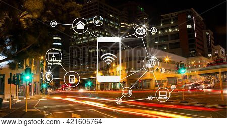 Composition of network of connections with icons over cityscape at night. global connections, networking and business concept digitally generated image.