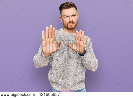 Young redhead man wearing casual winter sweater moving away hands palms showing refusal and denial with afraid and disgusting expression. stop and forbidden.