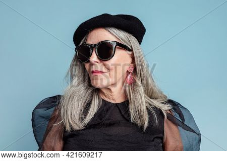 Cool grandma with an attitude in a beret and sunglasses