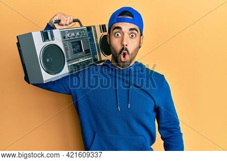 Young hispanic man holding boombox, listening to music scared and amazed with open mouth for surprise, disbelief face