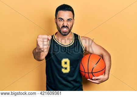Handsome hispanic man with beard holding basketball ball annoyed and frustrated shouting with anger, yelling crazy with anger and hand raised