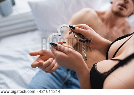 Cropped View Of Woman In Bra Holding Handcuffs Near Blurred Boyfriend On Bed.