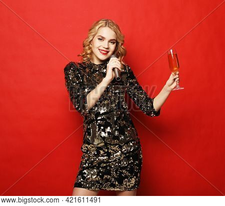 Party, holiday and people concept: Young luxury woman wearing evening dress holding glass of champagne and microphone. Dance and Karaoke. Party Time.