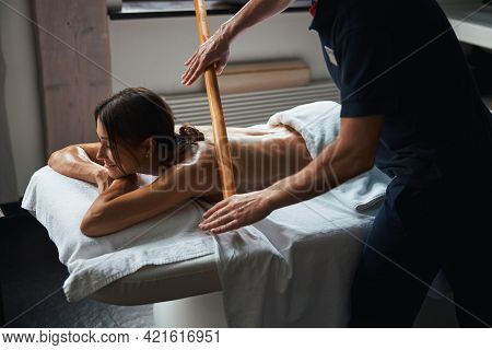 Beautiful Caucasian Young Woman Under The Towel Relaxing And Resting While Getting Manual Therapy Wi