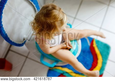Closeup Of Cute Little Toddler Baby Girl Child Sitting On Toilet Wc Seat. Potty Training For Small C