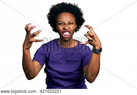African american woman with afro hair wearing casual purple t shirt shouting frustrated with rage, hands trying to strangle, yelling mad