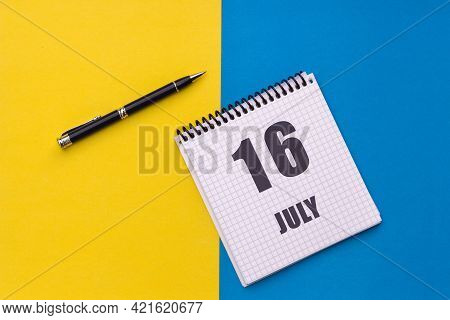July 16th. Day 16 Of Month, Calendar Date. Notebook With A Spiral And Pen Lies On A Yellow-blue Back