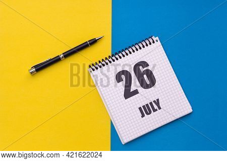 July 26th. Day 26 Of Month, Calendar Date. Notebook With A Spiral And Pen Lies On A Yellow-blue Back