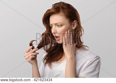 Red-haired Young Woman Looking At Damaged Hair Over Gray Background