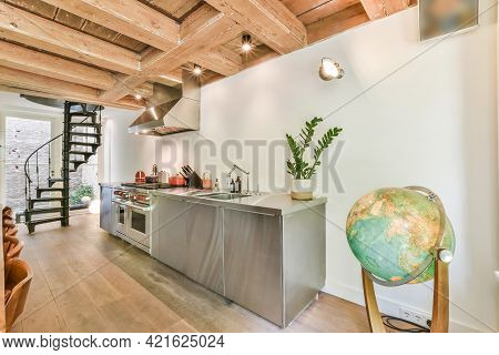 Shiny Chrome Cabinets And Appliances Of Modern Kitchen In Country House With Wood Beamed Ceiling And
