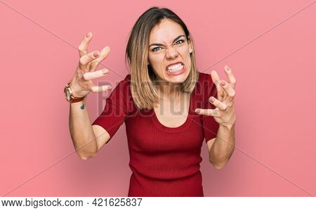 Young blonde girl wearing casual clothes shouting frustrated with rage, hands trying to strangle, yelling mad