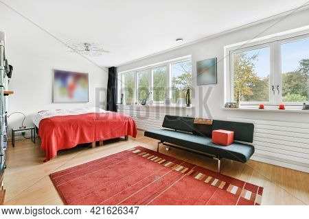 Simple Interior Of Bedroom Furnished With Table And Decorative Paintings On Wall In Soft Light