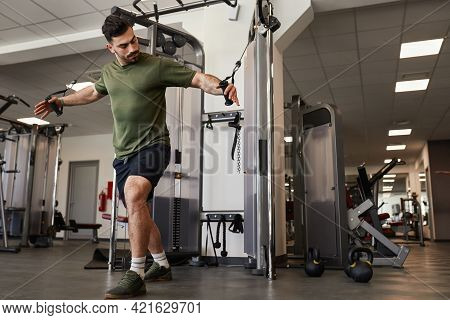 Handsome Muscular Bearded Fitness Guy Training His Chest By Doing Weighted Cable Extension Exercise.