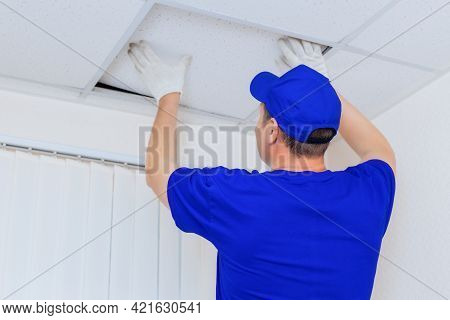 A Worker In Overalls Installs A Ceiling Tile Made Of Drywall In An Office Space. Advertising Photo O