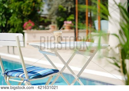 Ice Coffee Cyprus Frappe Fredo Against Blue Clear Water Of The Swimming Pool, On White Table, With M