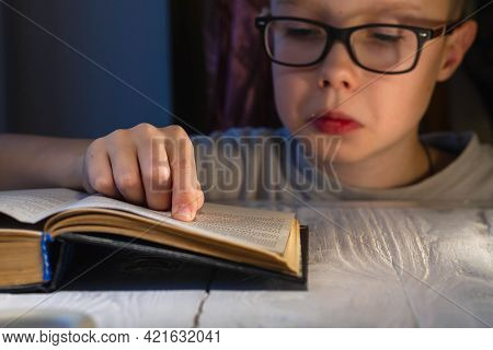 A Teenage Caucasian Boy With Glasses Is Having A Hard Time Reading A Book And Trying To Make Sense O