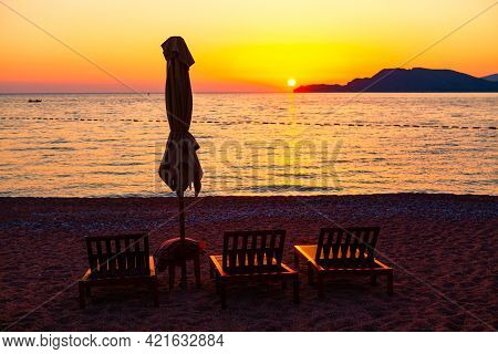Chaise Lounges And Umbrella On The Beach In The Twilight . Fantastic Coastal Summer Vacation . Beach