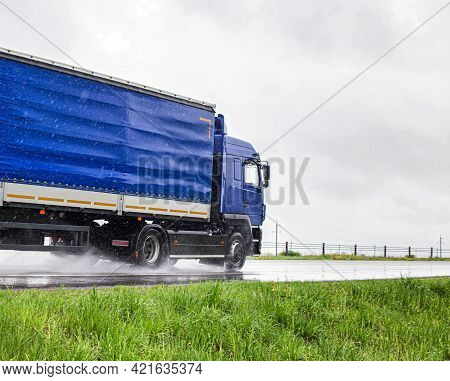 A Blue Semi-trailer Truck Drives On A Wet Highway During The Rain In Summer. The Concept Of Poor Vis