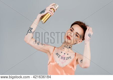 Young Tattooed Woman With Red Lips Holding Hairspray Isolated On Grey.