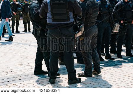 A Crowd Of Police Officers In Black Suits Stands Outdoor In The City. Rioting. Protest. Violation. P