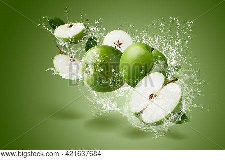 Water Splashing On Green Apple With Green Leaf And Cut Slice With Seed On Green Background.