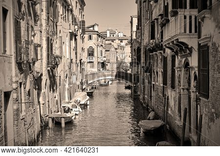 Canal in Venice with boats, Italy. Black and white sepia toned photography, venetian view