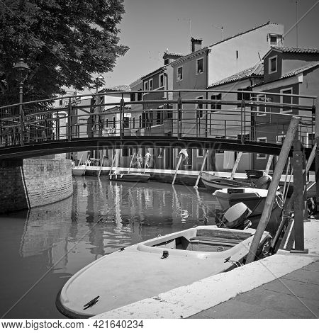Canal Burano in Venice with moored boats, Italy. Black and white photography, venetian view