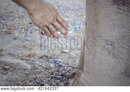 Man's Hand Holding A Water Bottle Watering A Big Tree. Concept Holy Of Buddhism Thai People
