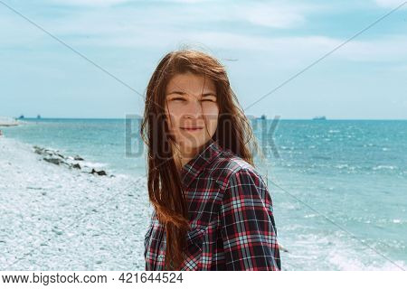 Summer Sun Shines Brightly On A Girl With Long Brown Hair On The Seashore