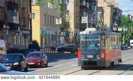 A Modern Single-carriage Tram Of Black And Red Colors On A City Street. Unusual Tuned Body. Paved Tr