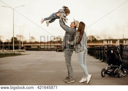 Stylish Young Family Dressed In Denim Clothes Walks Near The River With A Stroller. Dad Mom And Litt