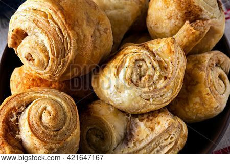 Closeup of fresh homemade puff pastry rolls baked with cinnamon.
