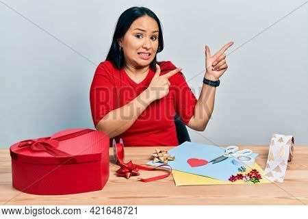 Beautiful hispanic woman with nose piercing doing handcraft creative decoration pointing aside worried and nervous with both hands, concerned and surprised expression