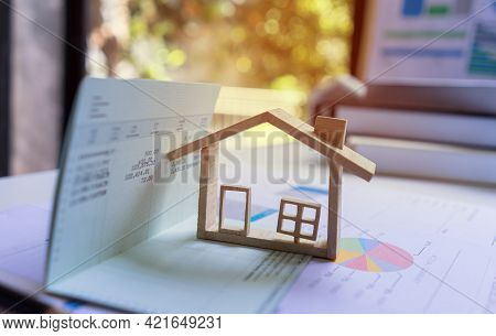Miniature Model House Located On Saving Account Passbook. Concept Of Money-saving For Housing.