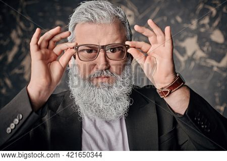 Strict  man with a gray beard looks through glasses with stern look. Vision and glasses concept.