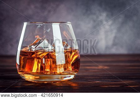 A Glass Of Whiskey On The Dark Brown Wooden Table. Transparent Yellow Alcoholic Beverage With Ice. B