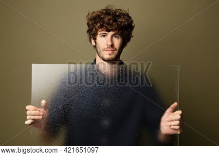 Man holding a translucent glass by the wall
