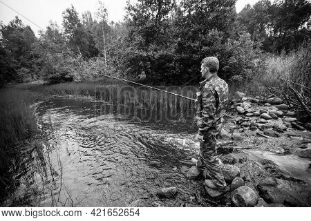 A man catching fish on the lake. Black and white photo.