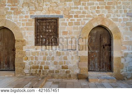 Two Weathered Wooden Arched Doors And One Closed Rusted Wrought Iron Window On Bricks Stone Wall And