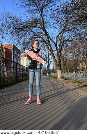 Cute Girl In Denim And Pink Sneakers Holds A Penny Board, A Longboard . International Skateboarding