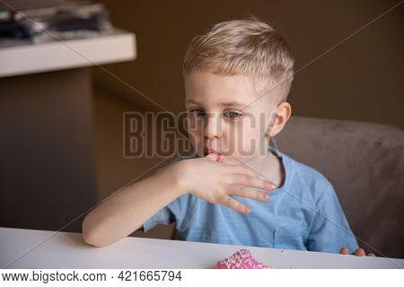 The Concept Is Useless Food. A Little Boy With Blond Hair Eats A Pink Doughnut At Home And Licks His