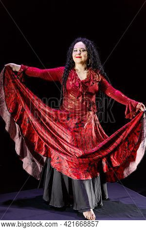 Barefoot Gypsy Woman With Long Black Hair Dances Waving Her Skirt. Vertical Photo