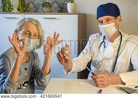 Caring Doctor And A Positive Elderly Grandmother In Masks At Home Or In The Hospital Show Ok. Concep