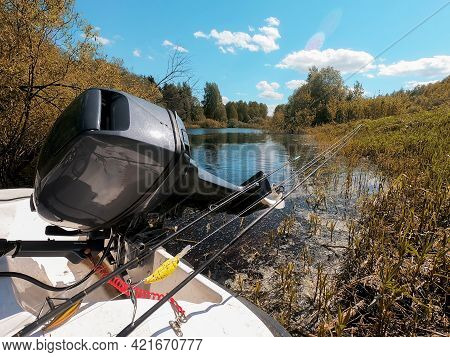 Outboard Motor In A Boat And Tackle For Fishing, Against The Background Of A River, Vegetation And A